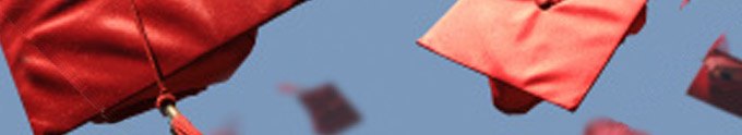 photograph of graduation hats flying.